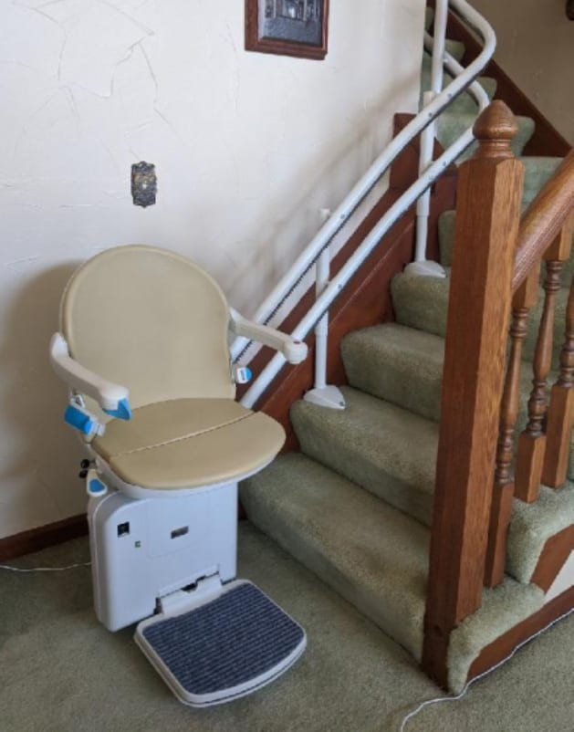 Handicare 2000 stairlift waiting at the bottom of the steps